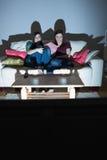 Deux amis heureux sur le divan regardant la TV ensemble dans l'obscurité Photographie stock