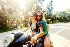 Deux amis heureux sur un vélo montent par la jungle tropicale Images stock