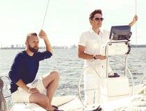 Deux amis heureux voyageant sur un yacht et appréciant un bon summe Photo stock