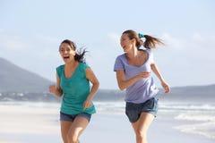 Deux amis insouciants courant sur la plage ensemble Photo libre de droits