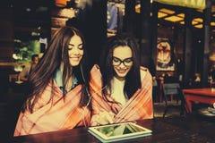 Deux amis intimes observant quelque chose sur un comprimé Photo stock