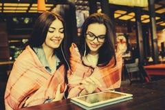 Deux amis intimes observant quelque chose sur un comprimé Photographie stock