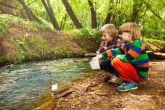 Deux amis jouant avec les bateaux de papier à la rive Images stock