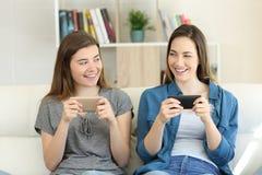 Deux amis jouant en ligne avec leurs smartphones Photographie stock libre de droits