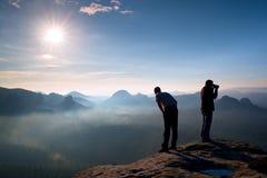Deux amis La pensée de randonneur et l'enthousiaste de photo prend le séjour de photos sur la falaise Paysage rêveur de vieille g Photographie stock libre de droits