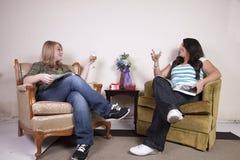 Deux amis lisant le magazine et buvant du vin Photographie stock