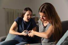 Deux amis luttant pour la TV à télécommande Images stock