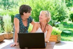 Deux amis mûrs de femmes à l'aide de l'ordinateur portable, sur la terrasse de jardin Images stock