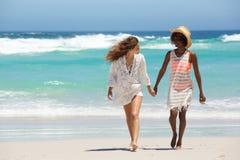 Deux amis marchant ensemble à la plage Photographie stock