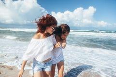 Deux amis marchant sur la plage Image stock