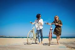 Deux amis marchant sur la plage avec des bicyclettes Photographie stock