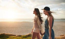 Deux amis marchant sur la plage un jour d'été Photographie stock