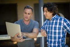 Deux amis masculins à l'aide de l'ordinateur portable Photo libre de droits