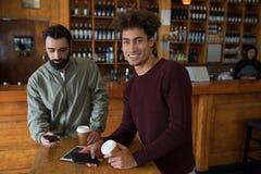 Deux amis masculins à l'aide du téléphone portable tout en ayant le café Image libre de droits