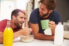 Deux amis masculins appréciant le petit déjeuner à la maison ensemble Images stock