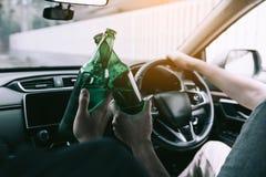 Deux amis masculins célèbrent dans la voiture tandis qu'ils font tinter la bouteille à bière ensemble photo libre de droits