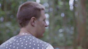Deux amis masculins caucasiens dans le T-shirt sont parlants et marchants dans Forest Park clips vidéos
