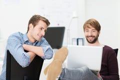 Deux amis masculins décontractés travaillant sur un ordinateur portable Image stock