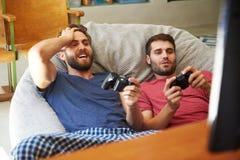Deux amis masculins dans des pyjamas jouant le jeu vidéo ensemble Photo libre de droits