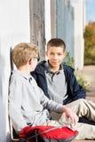 Deux amis masculins de la jeunesse s'asseyant dehors Image stock