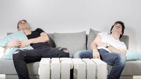 Deux amis masculins endormis sur l'entraîneur confortable gris à la maison Images stock