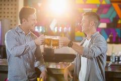Deux amis masculins grillant des tasses de bière au compteur de barre Photos stock