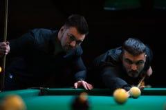 Deux amis masculins jouant le billard dans le club foncé Photo libre de droits