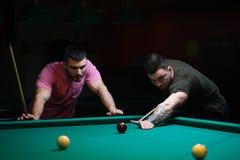 Deux amis masculins jouant le billard dans le club foncé Photo stock