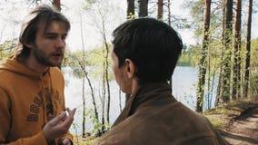 Deux amis masculins marchant sur la voie et les débuts de forêt discutant le jour ensoleillé banque de vidéos