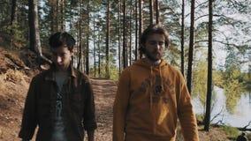 Deux amis masculins marchant sur le sentier piéton de forêt le jour ensoleillé banque de vidéos