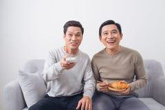 Deux amis masculins observant le football se reposer sur le sofa à la maison Photo stock