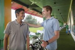 Deux amis masculins parlant et souriant tout en jouant le golf Images libres de droits