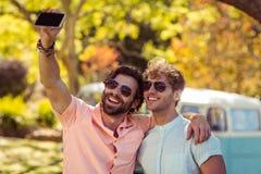 Deux amis masculins prenant le selfie avec le téléphone portable Images libres de droits