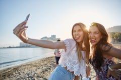 Deux amis masculins prenant le selfie sur la plage tirant des visages Images stock