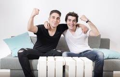 Deux amis masculins s'asseyant sur un sofa gris avec des coussins embrassent tout en faisant des gestes de la victoire Photographie stock