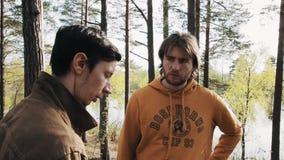 Deux amis masculins se tenant sur la voie et les débuts de forêt discutant le jour ensoleillé banque de vidéos