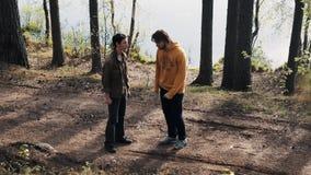 Deux amis masculins se tenant sur le sentier piéton et les querelles de forêt le jour ensoleillé banque de vidéos