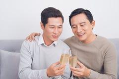 Deux amis masculins sont souriants et résonnants des verres de champagne o Photos stock