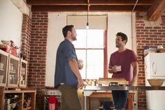 Deux amis masculins traînant dans la cuisine, angle faible Photos stock
