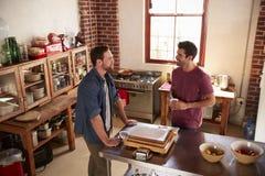Deux amis masculins traînant dans la cuisine, vue courbe Photos libres de droits