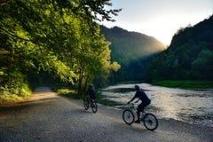 Deux amis montant des bicyclettes sur la rivière au coucher du soleil Image libre de droits