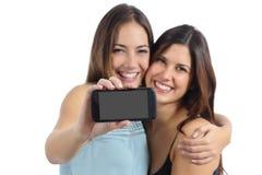 Deux amis montrant un écran intelligent vide de téléphone Photographie stock libre de droits