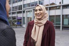 Deux amis musulmans britanniques de femmes se réunissant en dehors du bureau Photographie stock