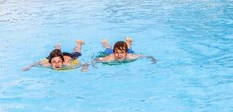 Deux amis nageant dans la piscine Photo stock