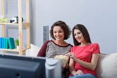 Deux amis observant le film à la maison Image libre de droits