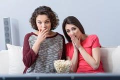 Deux amis observant le film à la maison Photographie stock