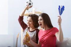 Deux amis observant le football à la maison Image stock