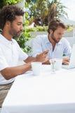 Deux amis occupés ayant le café ensemble Images stock