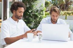 Deux amis occupés ayant le café ensemble Photos stock