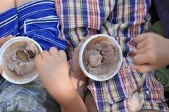 Deux amis ou familles heureux d'enfants, s'asseyant sur un banc mangeant la crème glacée  Photographie stock libre de droits